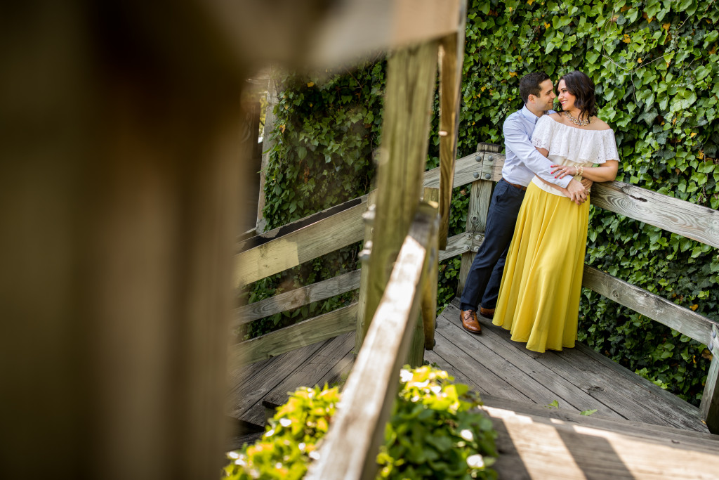 Adrianna and Steve stop for a kiss by a set of stairs hiding by a wall of ivy.